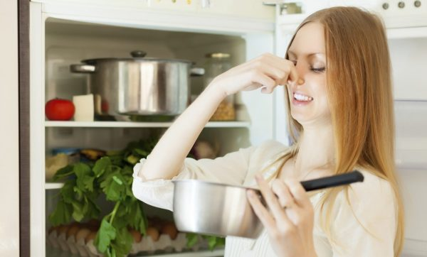Девушка проверяет еду в холодильнике