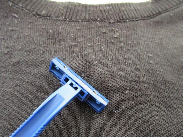 Бритвенный станок лежит на ткани с катышками