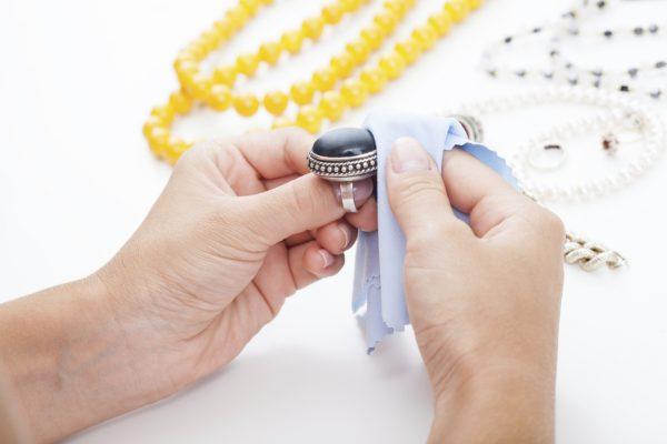 Девушка протирает кольцо тканевой салфеткой