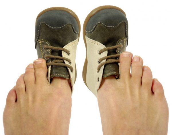 Детские башмачки надеты на большие пальцы взрослых ног