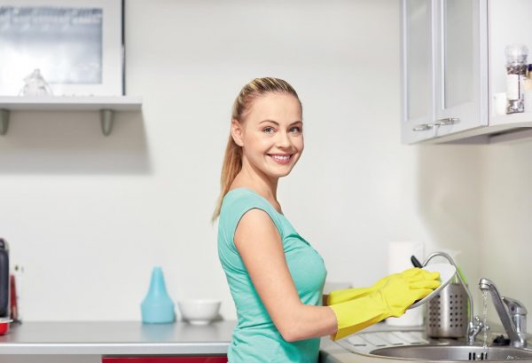 Девушка моет посуду и улыбается