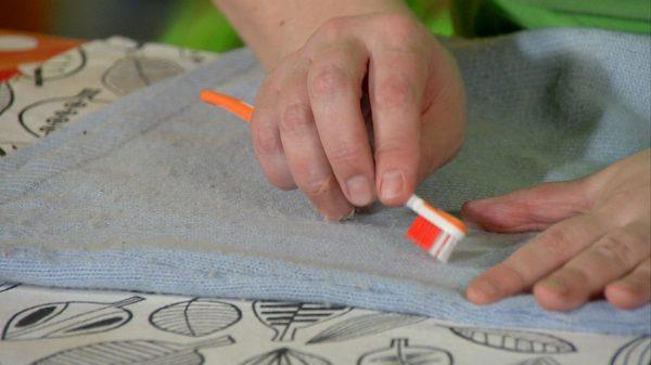 Удаление катышков со свитера с помощью зубной щётки