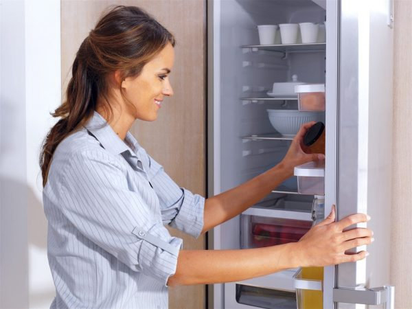 Женщина вытирает холодильник