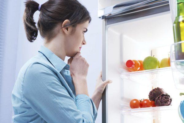 Девушка задумчиво смотрит на полки холодильника