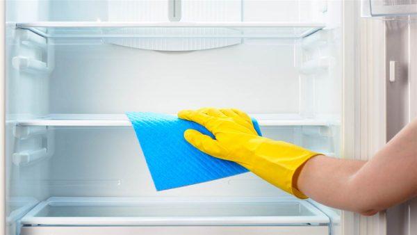 Мытьё холодильника рукой в перчатке