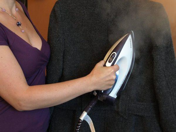 Женщина отпаривает пальто в вертикальном положении