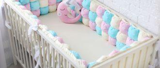 ребенок в кроватке с бортиками