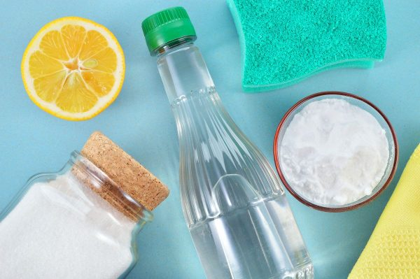 Сода, уксус, лимон, соль и губка на столе