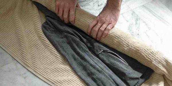 Пальто заворачивают в полотенце для сушки