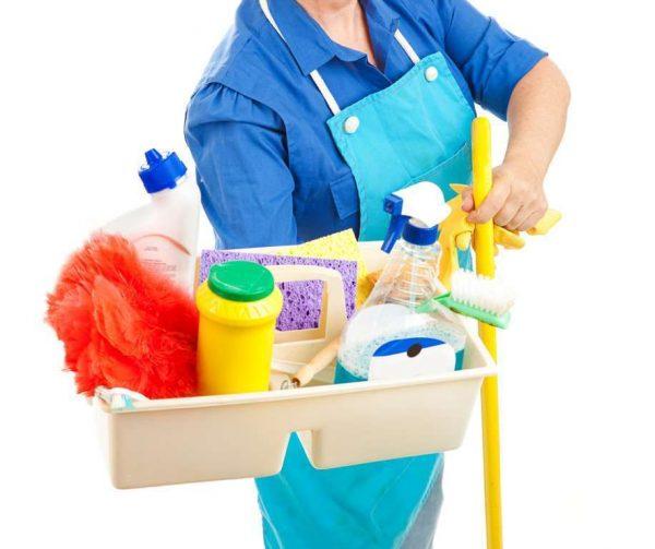 Женщина в фартуке держит контейнер с бытовой химией для уборки