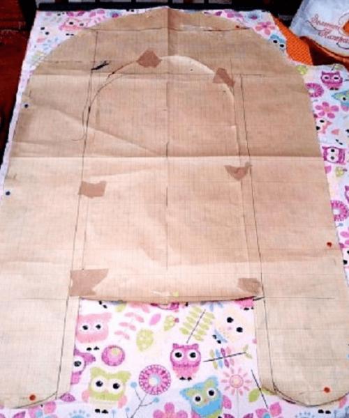 Бумажная выкройка разложена на отрезе ткани