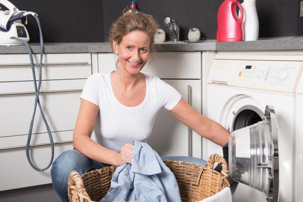 Женщина складывает вещи в стиральную машину