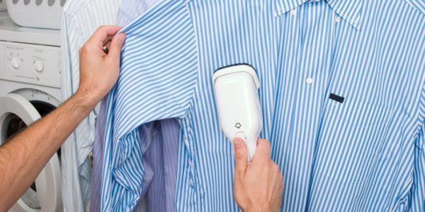 Мужчина отпаривает свою рубашку отпаривателем