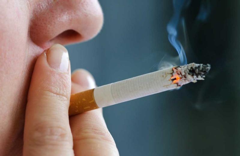 мужчина курит в постели