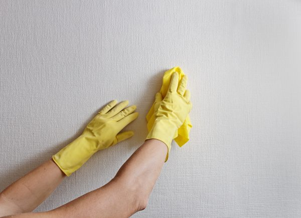 Девушка чистит обои