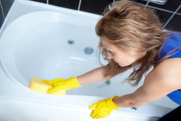 Девушка моет ванну в резиновых перчатках