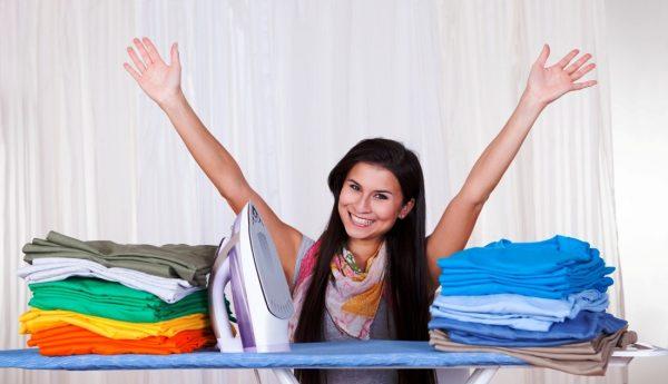Радостная девушка и две стопки вещей на гладильной доске