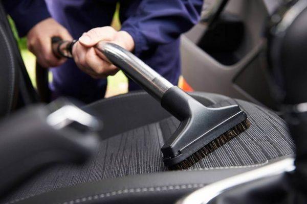 Чистят сиденье автомобиля пылесосом