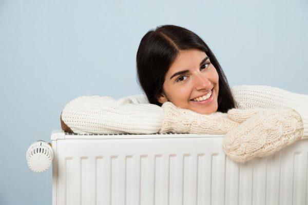Девушка в вязанном свитере обнимает батарею