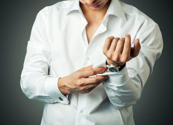 Мужчина застёгивает рубашку