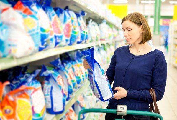 Женщина выбирает стиральный порошок в магазине