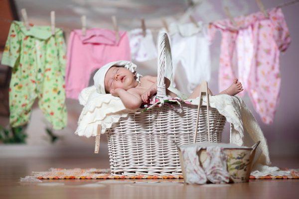 Новорождённый лежит в корзине с бельём