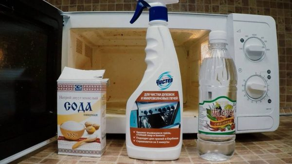 Сода, чистящий спрей и уксус на фоне микроволновки