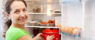 Женщина ставит в холодильник кастрюлю